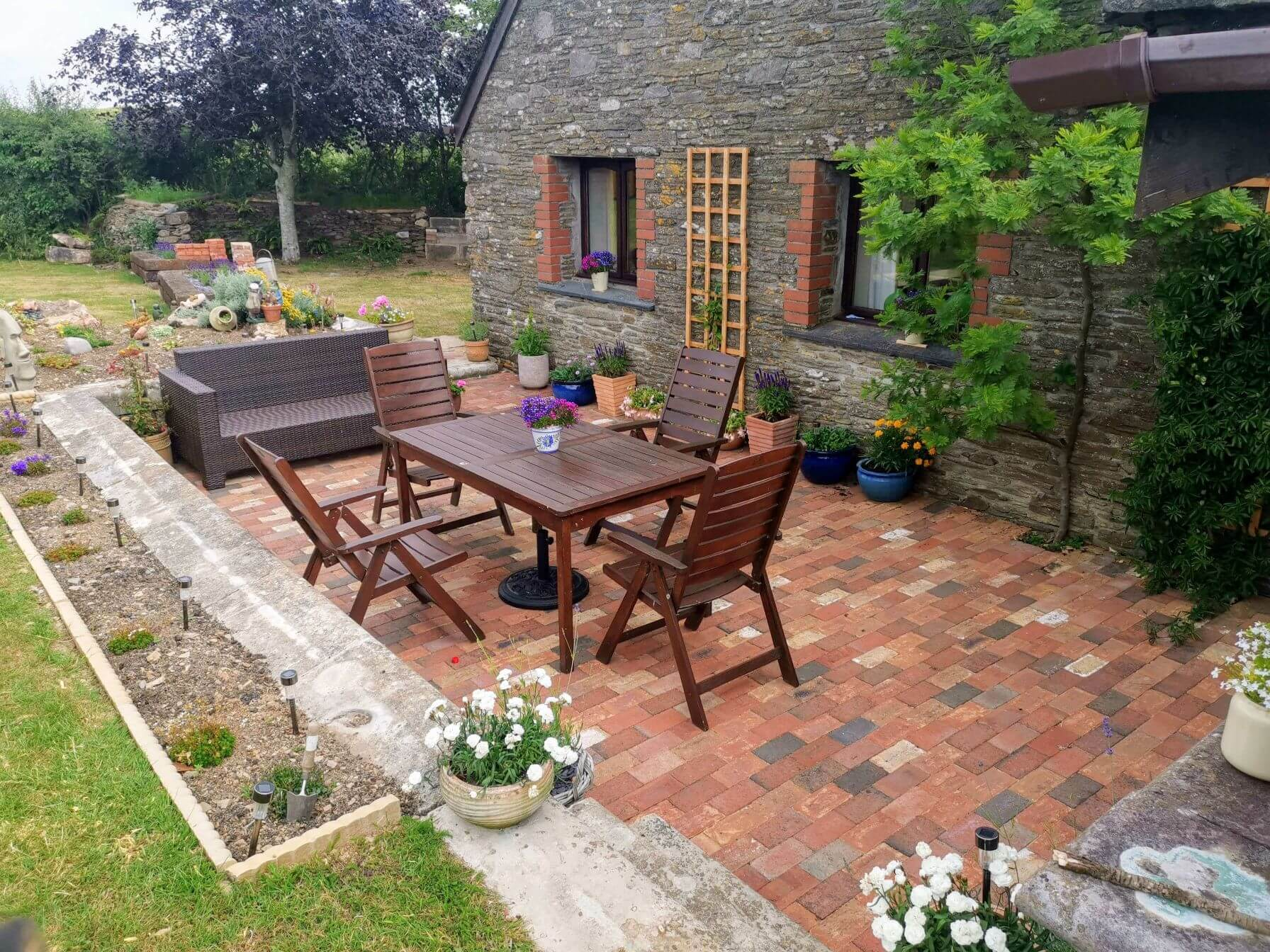 Landscaping Services Plymouth - Image of a garden following a makeover from Jackson Garden Services, featuring wooden garden furniture, flower beds, colourful plants and shrubs